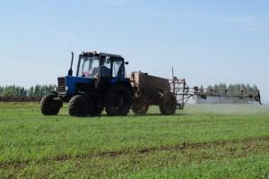 Трактор проводит химическую обработку поля